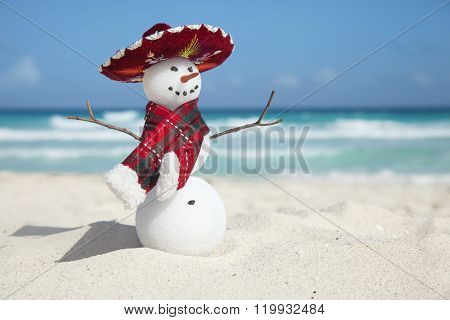 Miniature Snowman Wearing Mexican Sombrero And Scarf On The Beach