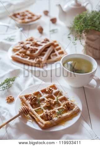 Belgian waffles sweet healthy dessert with honey, nuts, green tea.