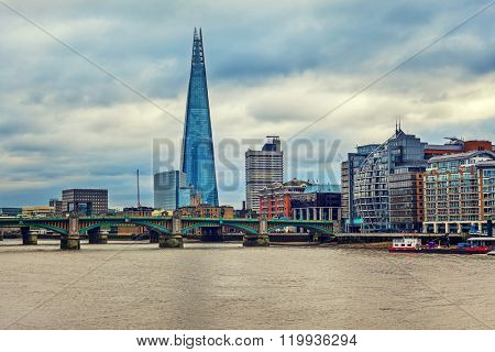 View of modern buildings along Thames river and Shard on background under cloudy sky in London, UK (toned).