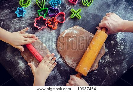 Mother And Daughter Using Rolling Pins Together In The Kitchen