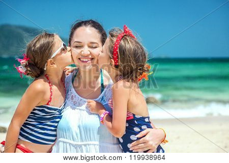 Mom with her two children having fun at the tropical beach, daughters kissing mother