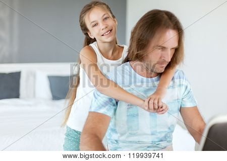 Pre teen daughter came to her dad when he was using laptop in home room. Father browsing internet with child together.