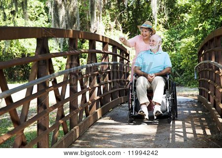 Senior woman pushing her disabled husband through the park in his wheelchair.