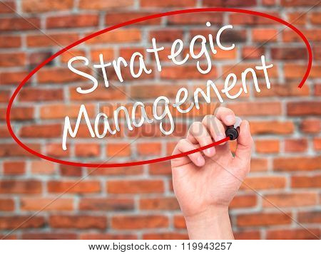 Man Hand Writing Strategic Management With Black Marker On Visual Screen.