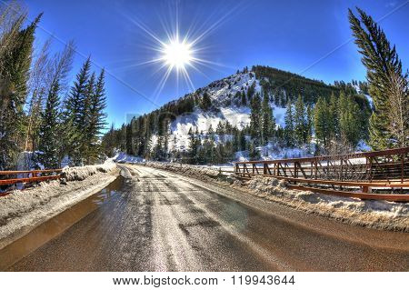 Amazing view of the sun over a snowy bridge road with a mountain landscape in Aspen