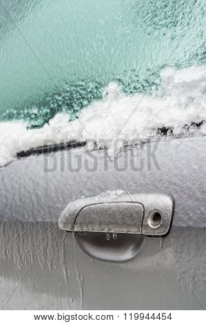 Car handle is covered with ice after freezing rain.