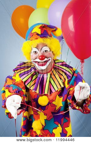 Clown with a bunch of helium balloons, holding a red one toward the camera.