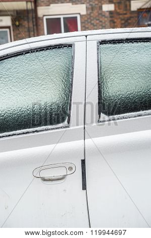 Car windows are covered with ice after freezing rain.