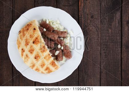 Cevapcici, bosnian minced meat kebab with diced onion and somun bread