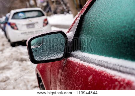 Car mirror and windows are covered with ice after freezing rain