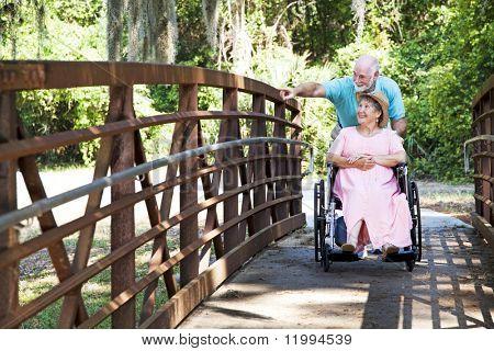 Senior man pushes his disabled wife's wheelchair through the park.