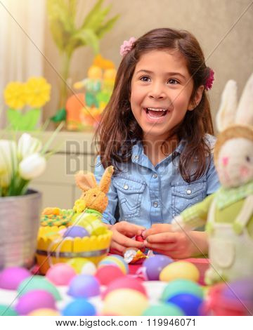 Portrait of cute little girl playing in daycare, painting eggs in different colors, with pleasure preparing to happy Easter holiday
