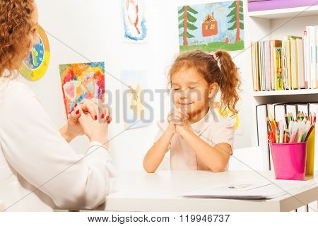 Schoolgirl closes her eyes and exercises putting fingers with teacher at the desk