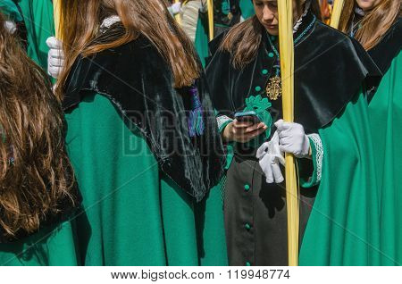 A Girl Using Her Mobile Phone During A Procession
