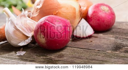 Vegetables, Garlic A Garden Radish And Onions, It Is Large Against From Gray Old Boards