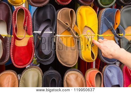 Hand Of Woman With Colorful Leather Shoes On Stall At The Bazaar