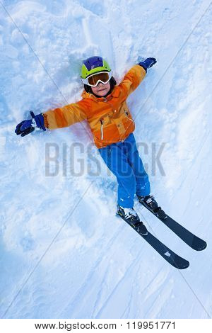 Little boy lay in snow and looking up with ski mask, mountain ski and helmet view from above