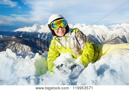 Happy skier woman rest laying in snow and smile