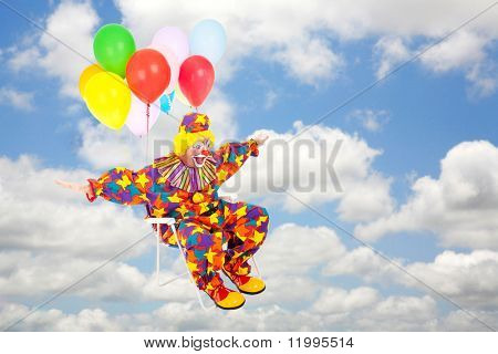Clown flies through the air on his lawn chair with balloons attached