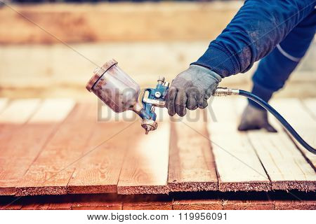Man Using Protective Gloves Painting Wooden Timber With Spray Paint Gun