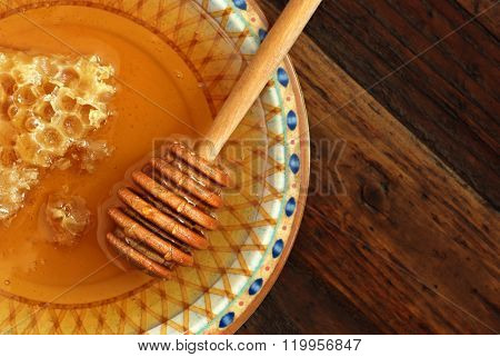 Rustic still-life of golden honeycombs with fresh honey and drizzler on decorative plate over dark wood background.  Top view. Closeup with selective focus and copy space.