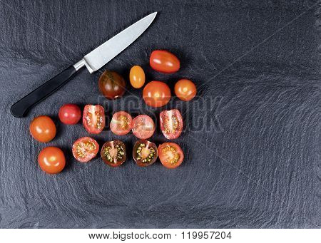 Colorful Mixed Small Tomatoes And Cutting Knife On Natural Black Slate Stone