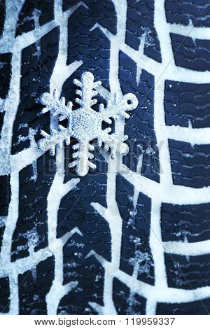 Winter tires in snow with snowflake, macro view