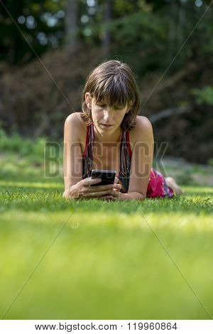 Young Woman Lying In Green Grass Using Her Smart Phone