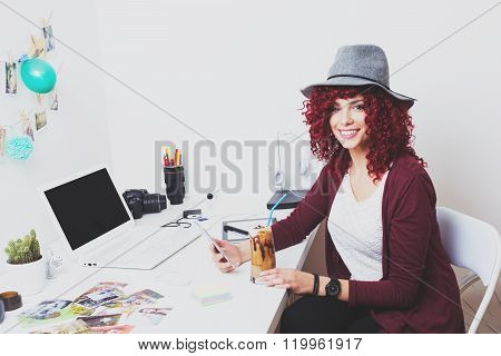 Modern female photographer in her home office with coffee and smartphone