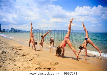 Cheerleaders Perform Hand Scale And Heel Stretch On Wet Sand