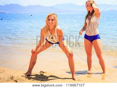 Girl Cheerleader Poses Hands On Knees Other Stands By On Sand