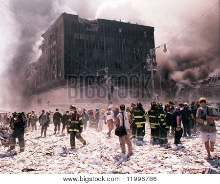 NEW YORK - SEPTEMBER 11:  New York City firefighters and journalists stand near the area known as Ground Zero after the collapse of the Twin Towers September 11, 2001 in New York City.