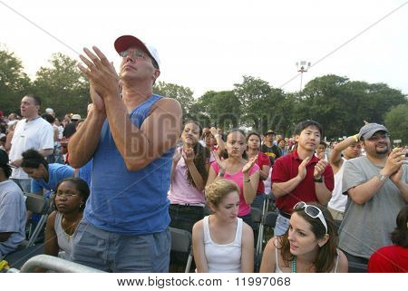 NEW YORK - JUNE 25: People clap as they pray on the second night of the Billy Graham Crusade at Flushing Meadows Corona Park on June 25, 2005 in Flushing, New York.