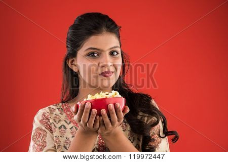 indian young and beautiful girl eating popcorn, asian girl enjoying popcorn or pop corn, isolated on