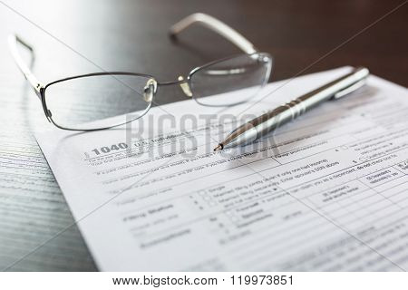 Tax form 1040 for individual tax return with pen and glasses