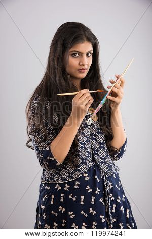 indian young girl with paint and brush and palate, asian art student, pretty indian girl painting, i