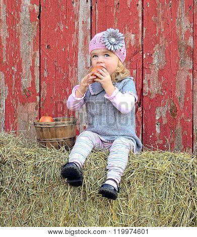 little girl eating apple on hay bale
