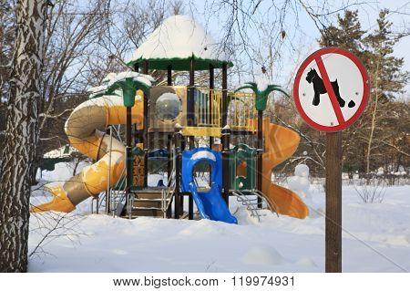 Sign forbidding dog walking on children's sports playground.