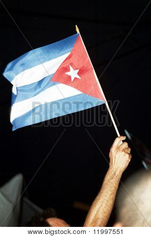 LITTLE HAVANA, FL - APRIL 14: A protester holds up a Cuban flag near the family home of Elian Gonzalez on April 14, 2000 in Little Havana, Florida. Elian was forcibly taken into custody on April 22.