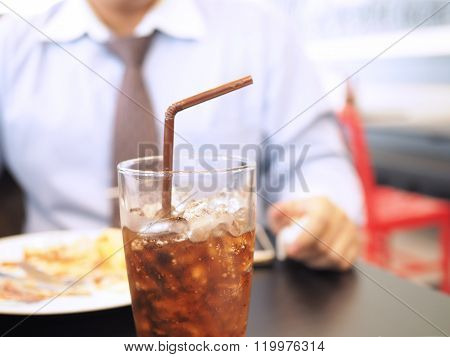 Fat And Unhealthy Businessman Having Soft Drink And Junk Food (focus On Soft Drink, Blurred Out The