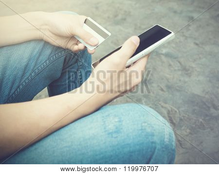 People Holding A Credit Card And Using Smartphone To Make Mobile Payment.