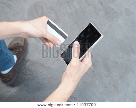 People Holding A Credit Card And Using Smartphone To Make Mobile Payment. (focus On Credit Card)