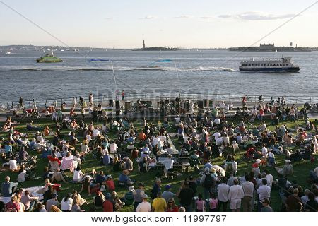 NEW YORK - JULY 1: Audience members watch as blues singer John Hammond performs with his band at Wagner Park on July 1, 2010 in New York City.