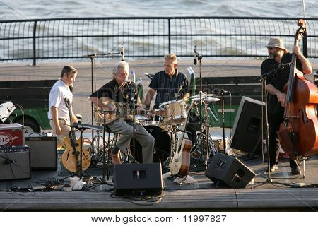 NEW YORK - JULY 1: Blues singer John Hammond (Center-L) performs at Wagner Park with drummer Neil Gouvin (C) and bassist Marty Ballou (R) on July 1, 2010 in New York City.