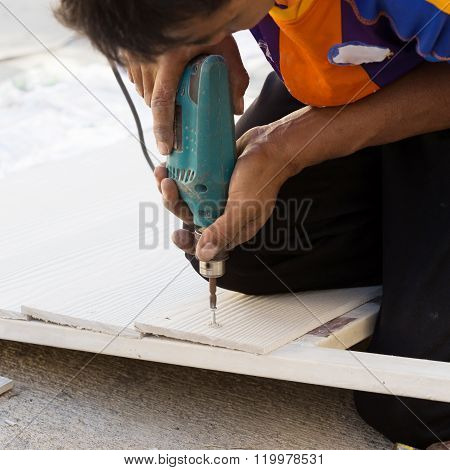 Carpenter Hands Using Electric Drill On Wood At Construction Site