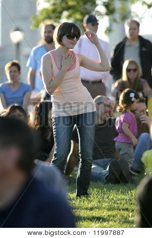 NEW YORK - JULY 1: A fan dances while blues singer John Hammond performs at Wagner Park on July 1, 2010 in New York City.