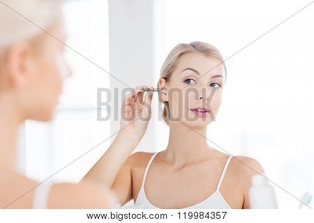 beauty, hygiene and people concept - young woman cleaning ear with cotton swab and looking to mirror at home bathroom