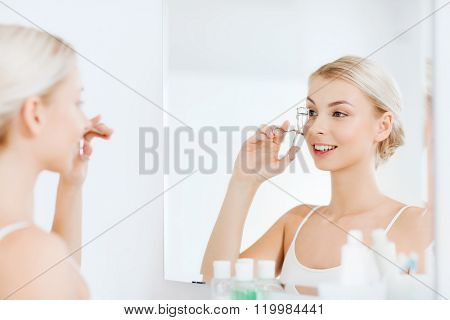 beauty, make up, cosmetics, morning and people concept - smiling young woman with curler curling eyelashes and looking to mirror at home bathroom