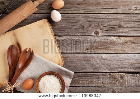 Kitchen table with cookbook, utensils and ingredients. Top view with copy space