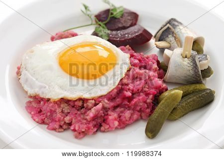 homemade labskaus, Northern Germany cuisine labskaus with fried egg, pickled gherkin, beetroot and rollmops